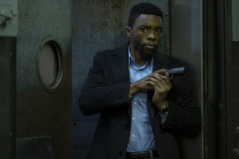 Chadwick Boseman de terno preto aberto e camisa azul segurando revólver
